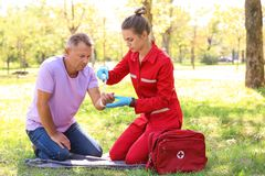 Woman in uniform applying bandage on man`s hand outdoors stock photography