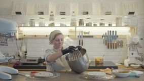 Experienced woman in uniform and black gloves stand in the modern kitchen with many kitchen utensils around and put. Woman in uniform and black gloves stand in stock video footage