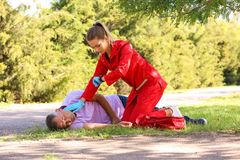 Woman in uniform checking pulse of unconscious man outdoors. Woman in uniform checking pulse of unconscious men outdoors. First aid stock photography