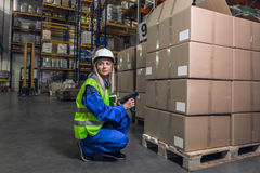 Woman in uniform holding device crouching stock photos