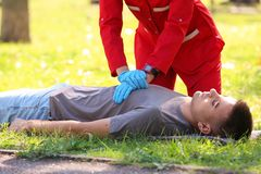 Woman in uniform performing CPR on unconscious man outdoors. First aid royalty free stock images