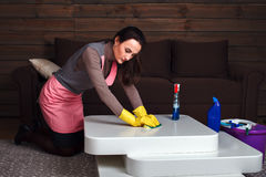 Woman in uniform and rubber gloves cleans table Royalty Free Stock Images