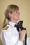 Woman in uniform tying necktie Stock Photography