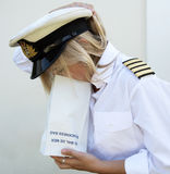 Woman in uniform using sickness  bag Stock Photos