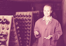 Woman in uniform working with bottle storage racks in winery cel Stock Photo