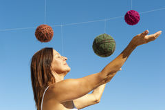 Woman and a universe of wool balls Royalty Free Stock Photography