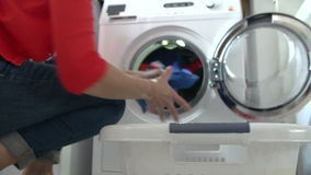 Woman Unloading Clothes From Washing Machine Stock Photo