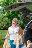 Woman unloading the groceries. Woman unpacking grocery bags from the back of the car Stock Photos