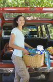 Woman unloading parked SUV on family camping trip, carrying picnic hamper, smiling, portrait Royalty Free Stock Image