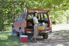 Woman unloading parked SUV on family camping trip, carrying picnic hamper, smiling, portrait Stock Photos