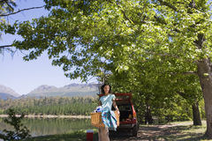 Woman unloading provisions from parked SUV on lakeside camping trip, carrying picnic hamper, smiling, portrait Royalty Free Stock Image