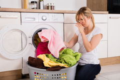 Woman Unloading Smelly Clothes From Washing Machine. Young Woman Looking At Smelly Clothes Out Of Washing Machine In Kitchen royalty free stock photo