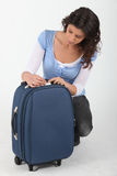 Woman unlocking a suitcase Royalty Free Stock Photography