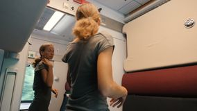 A young woman looks to a peephole modern comfortable train compartment. Then she unlocks and opens a mirror door with. A woman unlocks and opens a mirror door stock video