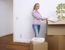 Woman unpacking boxes Royalty Free Stock Images