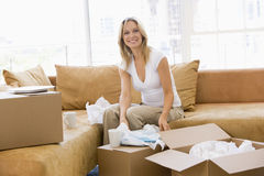 Woman unpacking boxes in new home smiling Stock Image