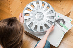 Woman unpacking car hub covers - inspecting the purchase Stock Image