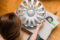 Woman unpacking car hub covers - inspecting the purchase Royalty Free Stock Photography
