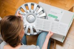 Woman unpacking car hub covers reading instruction Royalty Free Stock Image