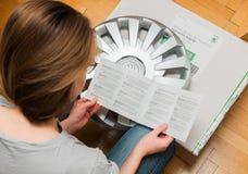 Woman unpacking car hub covers reading manual Royalty Free Stock Image