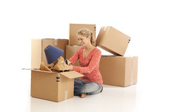 Woman unpacking cardboard boxes Stock Images