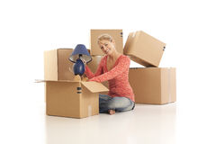 Woman unpacking cardboard boxes Stock Photos