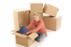 Woman unpacking cardboard boxes Stock Photo