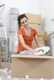 Woman unpacking cardboard boxes Royalty Free Stock Photography