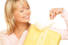 Woman unpacking gift. Portrait of young smiling woman unpacking gift isolated on white background Stock Photography