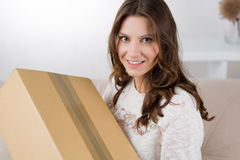 Woman unpacking her online order in the living room Stock Photos