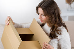 Woman unpacking her online order in the living room.  Royalty Free Stock Image