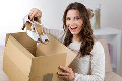 Woman unpacking her online order in the living room Royalty Free Stock Image