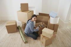 Woman Unpacking Moving Box stock photos