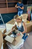 Woman unpacking moving boxes stock photography