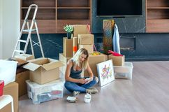 Woman unpacking moving boxes stock photos
