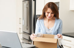 Woman Unpacking Online Purchase At Home. Woman Unpacks Online Purchase At Home Royalty Free Stock Photography