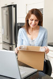 Woman Unpacking Online Purchase At Home. Woman Unpacks Online Purchase At Home Stock Photos