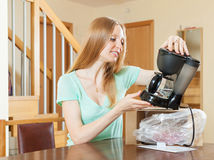 Woman unpacking and reading manual for new coffeemaker at home i Royalty Free Stock Images