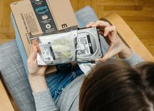 Woman unpacking unboxing Amazon Prime cardboard box HDD. PARIS, FRANCE - NOV 4, 2017: Woman POV unboxing on the living room armchair the Amazon Prime cardboard stock image