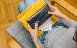 Woman unpacking unboxing Amazon Prime cardboard box. PARIS, FRANCE - NOV 4, 2017: Curious woman unboxing on the living room armchair the Amazon Prime cardboard royalty free stock photography