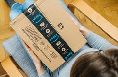 Woman unpacking unboxing Amazon Prime cardboard box scotch sealing tape. PARIS, FRANCE - NOV 4, 2017: Woman unboxing on the living room armchair the Amazon Prime royalty free stock image