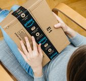Woman unpacking unboxing Amazon Prime cardboard box scotch sealing tape stock photos