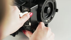 Woman Unplugging a Black Cable From a Video Camera stock video footage