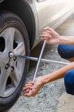 Woman are unscrew power to change tire by two hands Royalty Free Stock Images