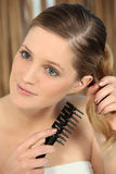 Woman untangling her hair Stock Photography