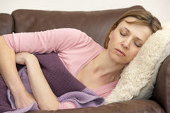 Woman Unwell And Lying On Sofa Royalty Free Stock Photos
