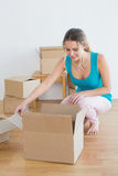Woman unwrapping boxes in new house Royalty Free Stock Images