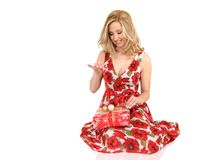 Woman unwrapping present. Attractive young woman with red floral dress unwrapping Christmas present, white studio background Royalty Free Stock Photos