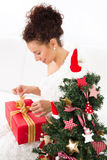 Woman unwraps christmas gift Stock Photography