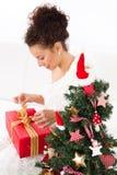 Woman unwraps christmas gift Stock Photography